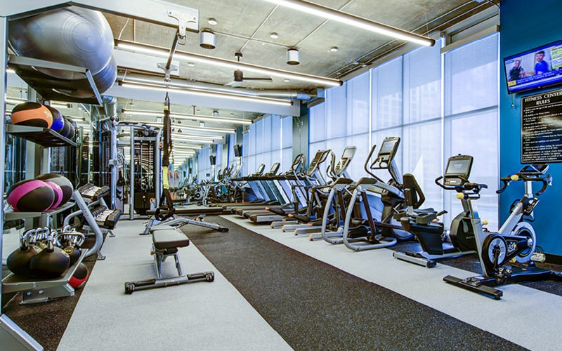 bright, sun lit fitness center with free weights and benches