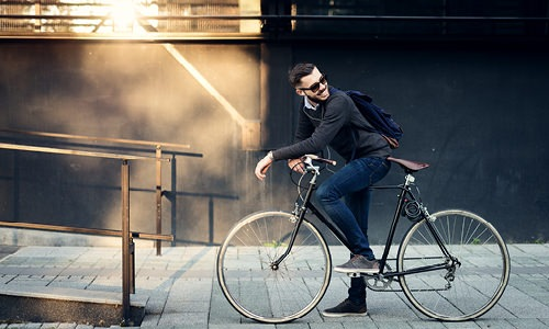 casually dressed man smiling on bicycle on the city sidewalk